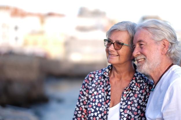 カメラを見て日没の夕暮れの海で屋外で笑っている美しい年配のカップル。白人カップル白髪