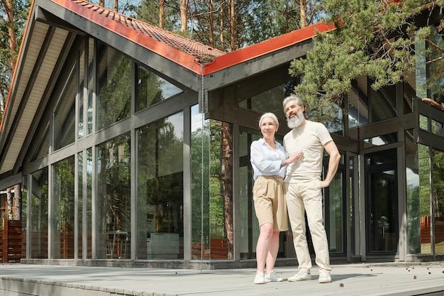 ガラスのコテージに立ち向かい、屋外で抱き合う美しい老夫婦