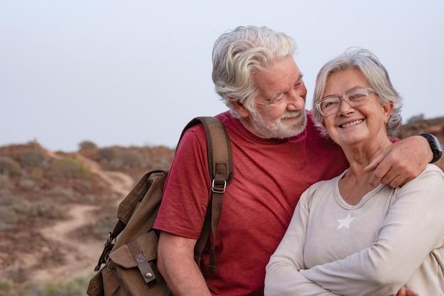 夕焼けの光で田舎を歩いて、幸せそうに笑って美しい年配のカップル。屋外と自然を楽しんで抱き締める妻と夫の白い髪の老夫婦