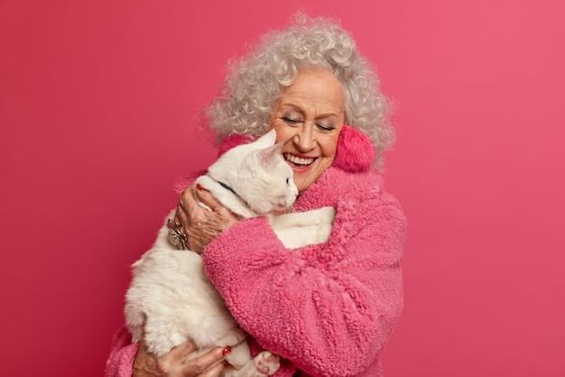 Beautiful senior grey haired woman carries white cat on hands, cares about own pet with love, dressed casually, isolated over pink wall, spends free time together, stay at home during quarantine