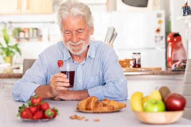 Beautiful senior man white hair having breakfast at home, drinking a juice of strawberries