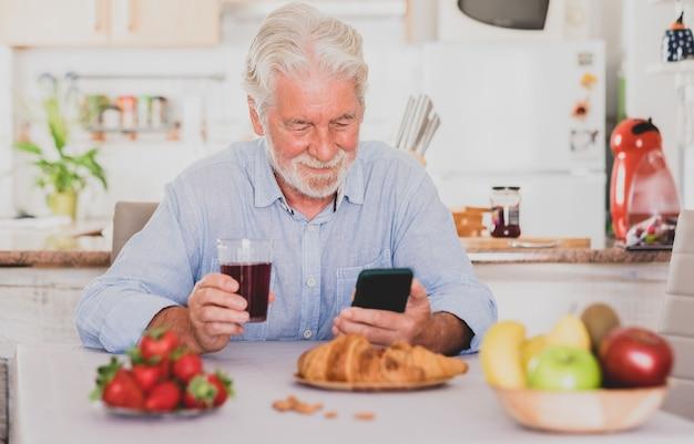 Beautiful senior man white hair having breakfast at home looking social media on smart phone.