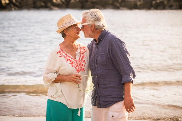 아름다운 수석 성숙한 부부는 키스와 함께 즐기고 휴가 또는 새로운 은퇴 생활 동안 해변에서 야외 여가 활동을 포옹