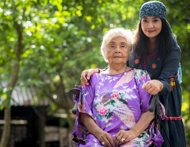 Красивая старшая мама и ее взрослая дочь обнимаются,