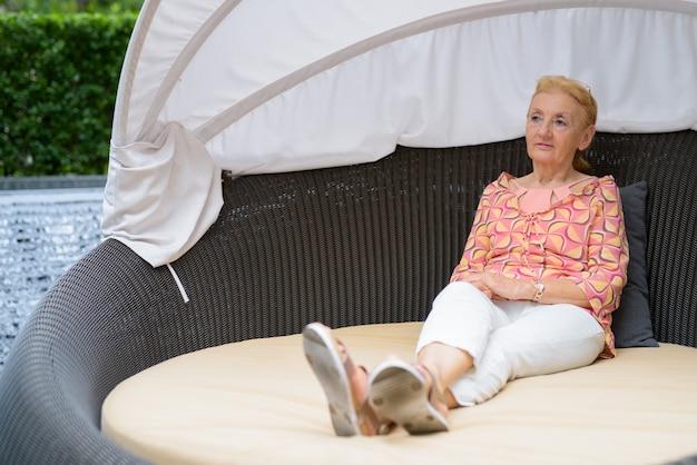 リラックスしたブロンドの髪を持つ美しいシニア観光女性