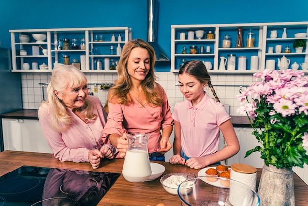 Красивая старшая женщина и семейная выпечка на кухне. бабушка готовит десерты дома с дочерью и племянником.