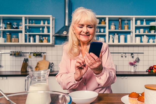 キッチンで焼く美しい年配の女性祖母が家でデザートを準備するベーキング料理と健康的な食事についての概念