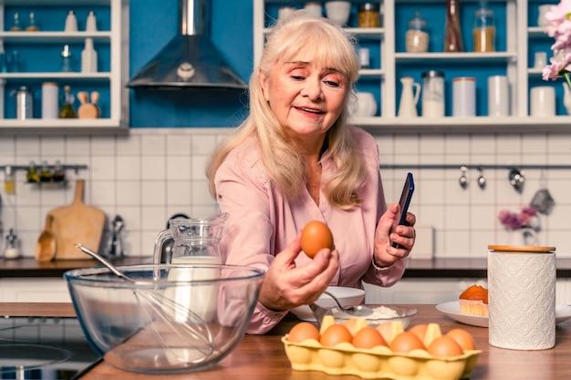 キッチンで焼く美しい年配の女性