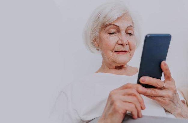잠들기 전에 휴대폰으로 소셜 네트워크 앱을 확인하는 아름다운 노년 여성