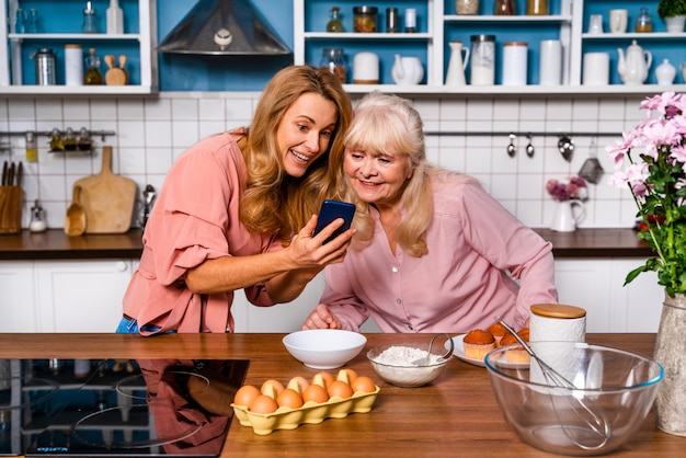 Beautiful senior woman and daughter baking in the kitchen  grandmother preparing desserts at home with family and looking at recipe on the internet