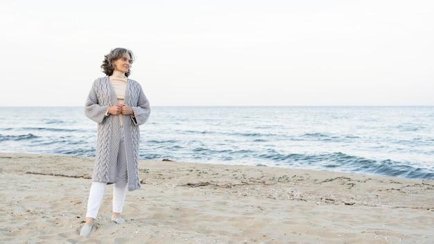 ビーチでの時間を楽しんでいる美しい年配の女性
