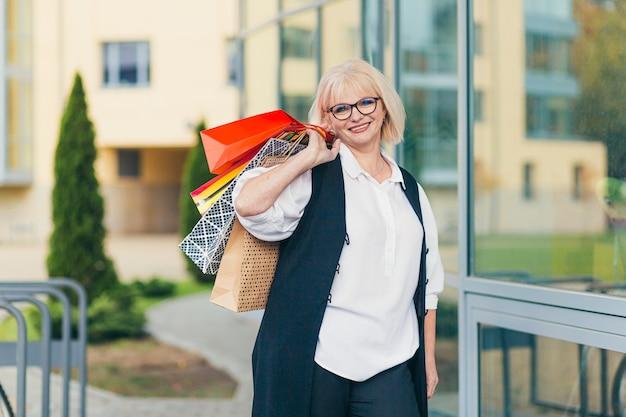 Красивая старшая женщина, держащая цветные сумки для товаров и подарков на фоне супермаркета