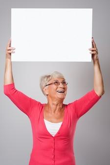 頭の上にホワイトボードを保持している美しい年配の女性
