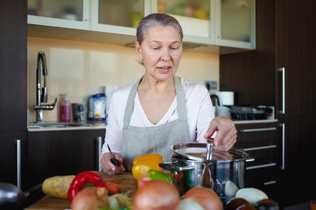 食事を準備するキッチンでエプロンの美しい年配の女性