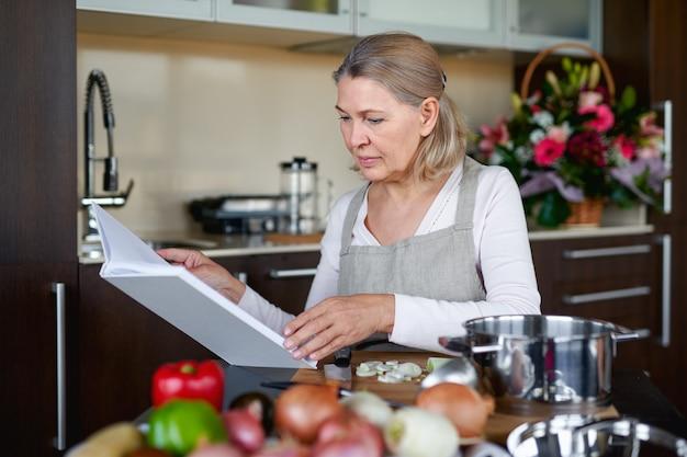 앞치마에 아름다운 수석 여자는 부엌에서 요리하는 동안 조리법 책을 읽고 있습니다