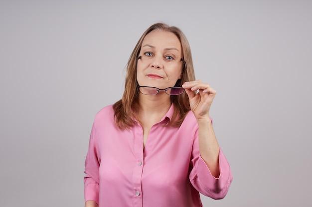 ピンクのブラウスを着た美しい年配の女性が眼鏡を脱ぐ