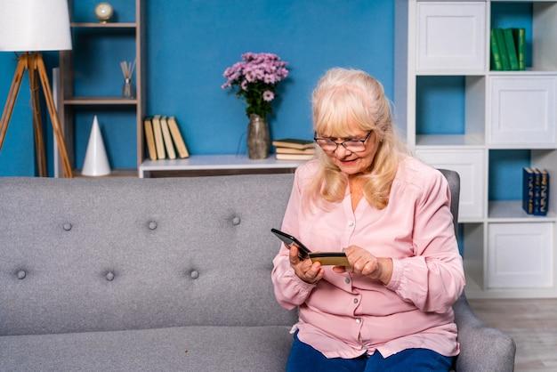 스마트 폰 장치로 인터넷에서 서핑하는 60 세 이상 휴대 전화 예쁜 성인을 사용하는 법을 배우는 아름다운 수석 여자