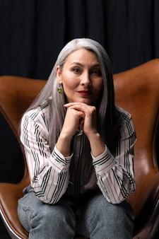 Красивый старший женский портрет позирует на стуле