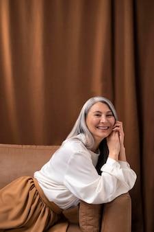 Красивый старший женский портрет позирует на диване