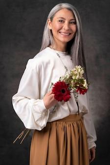 Bello ritratto senior della donna con i fiori