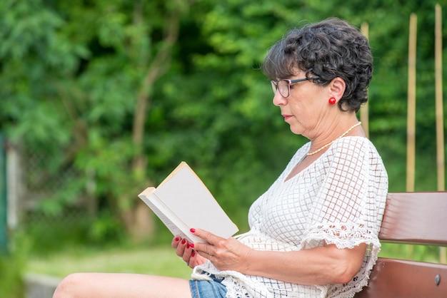 Beautiful senior woman reading book in the garden