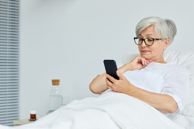 Beautiful senior woman relaxing on bed in hospital ward surfing internet on smartphone