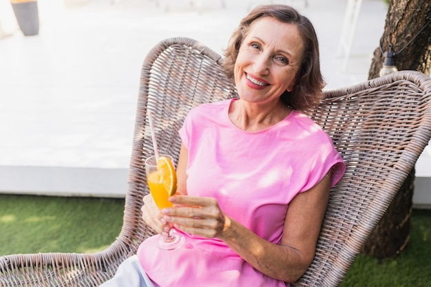 Beautiful senior woman relaxing at home in the garden - pretty mature lady rests in a peaceful backyard garden