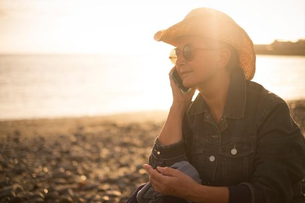 아름 다운 수석 여자는 일몰 동안 해변에서 전화에 말한다. 놀라운 황금빛 따뜻한 백라이트. 야외 생활 레저 개념 작업 및 바다 근처에 살고. 훌륭하게 살 수있는 자연적인 장소