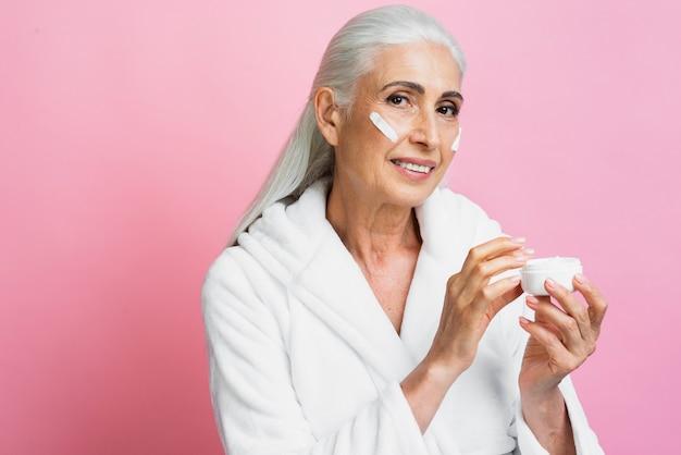 Beautiful senior woman testing cream