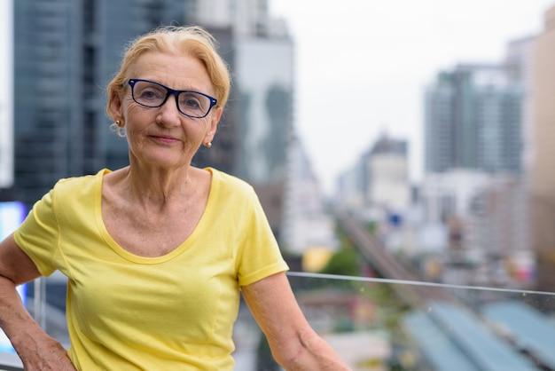 街の景色に対してブロンドの髪を持つ美しい年配の女性