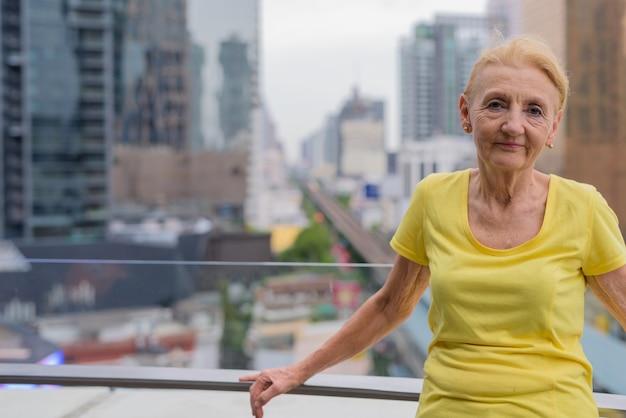 街の景色を望む金髪の美しい年配の女性