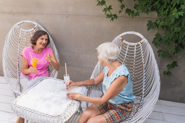 Beautiful senior women relaxing at home in the garden - two pretty mature ladies rest in a peaceful backyard garden