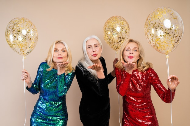Beautiful senior women with festive elgant dress having fun at a party