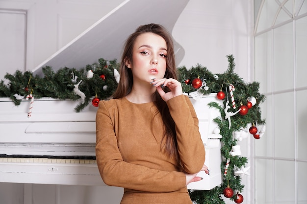 Beautiful sensual brunette girl with long straight hair near a white piano with christmas decoration