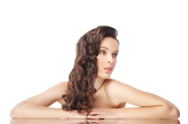 Красивая чувственная брюнетка с длинными волнистыми волосами и отражением - изолированные на белом