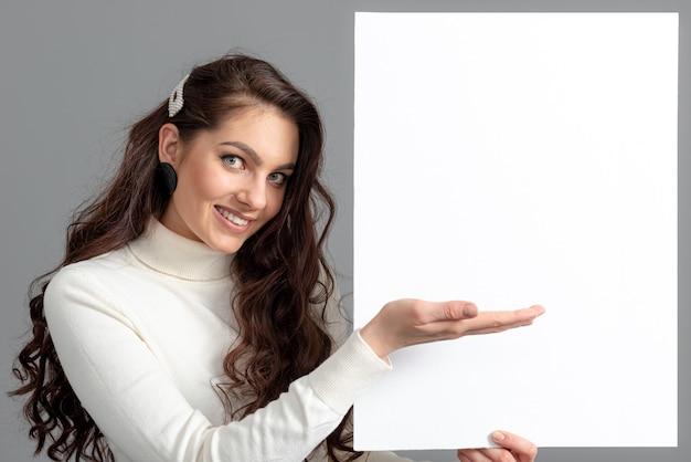 긴 곱슬 머리를 가진 아름 다운 관능적 인 비즈니스 여자는 회색, 복사 공간에 고립 된 빈 bilboard를 보여줍니다