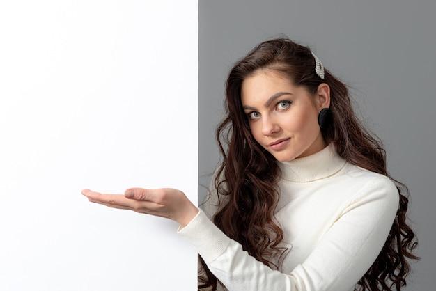 긴 곱슬 머리를 가진 아름 다운 관능적 인 비즈니스 우먼 회색, 복사 공간에 고립 된 빈 bilboard를 보여줍니다
