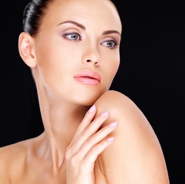 Bel viso sensuale della donna adulta con pelle fresca - su sfondo nero