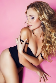 Beautiful sensual gorgeous young blonde lady with fashion make up and hairstyle posing in black bodysuit. girl with wavy hair. stylish lady isolated on pink .