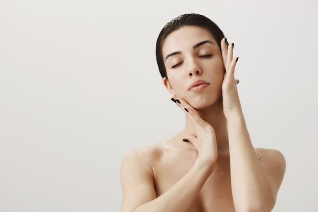 Bella donna sensuale in piedi nuda con gli occhi chiusi, toccando delicatamente il viso per applicare il prodotto per la cura della pelle
