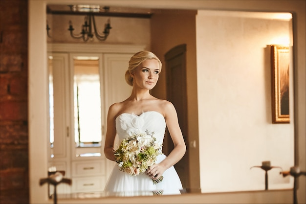 Beautiful and sensual young bride, sexy blonde model girl with charming smile and with bouquet of flowers in her hands in white dress posing in interior, wedding preparation in the morning