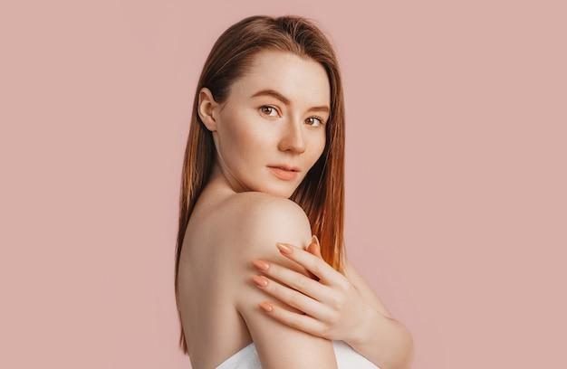 분홍색 배경에 깨끗한 피부를 가진 아름다운 관능적인 어린 소녀가 흉내를 내고 있습니다. 수건에 토플리스 여자입니다. 스파 트리트먼트, 자연의 아름다움과 관리, 젊음, 크림과 마스크, 신선함의 개념