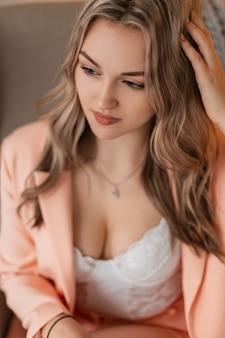 Красивая чувственная молодая девушка с волосами в модном блейзере и кружевном белом нижнем белье с пышной грудью сидит в кресле