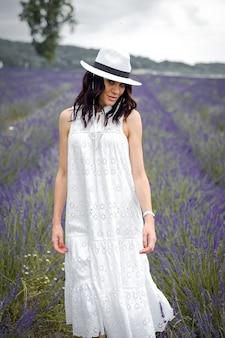 라벤더 밭에 모자와 흰 드레스를 입은 아름다운 관능적 인 젊은 여성