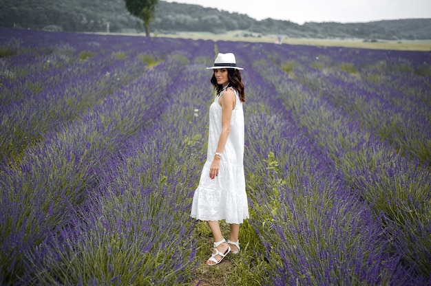 Beautiful sensual young woman with hat and white dress on the lavender field