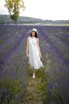 Beautiful sensual young woman with hat and white dress on the lavender field Premium Photo