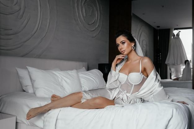 長い髪のメイクアップ、美しい官能的な若い女性は、花嫁の朝、ベッドの上の白いローブに横たわっています