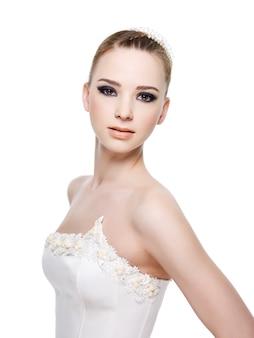 ウェディングドレスを着ている美しい官能的な花嫁。白で隔離。
