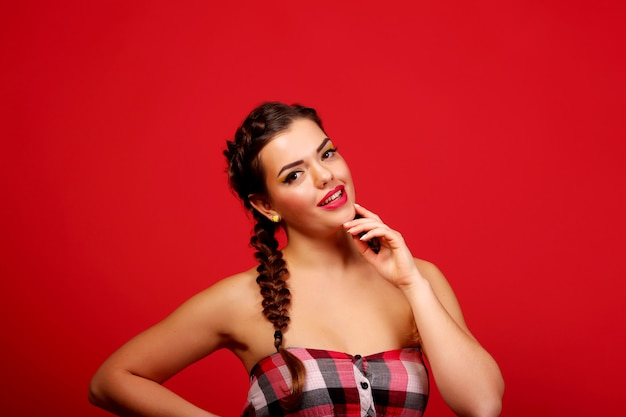Beautiful sensuality elegance lady brunette face woman, has brown eyes, curly gloss hair, sexy smiling lips. portrait. nature romantic pure makeup. red wall. beauty hairstyle.