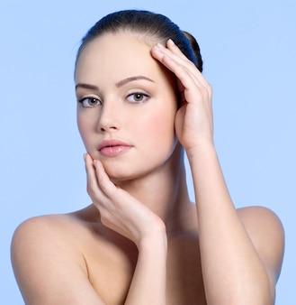 Красивое лицо чувственности молодой женщины на синем